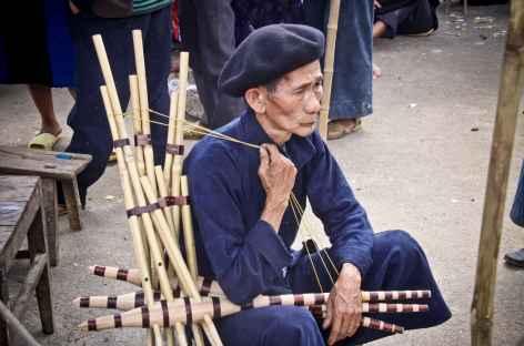 Un Hmong Noir vend des instruments de musique sur le marché de Dong Van -