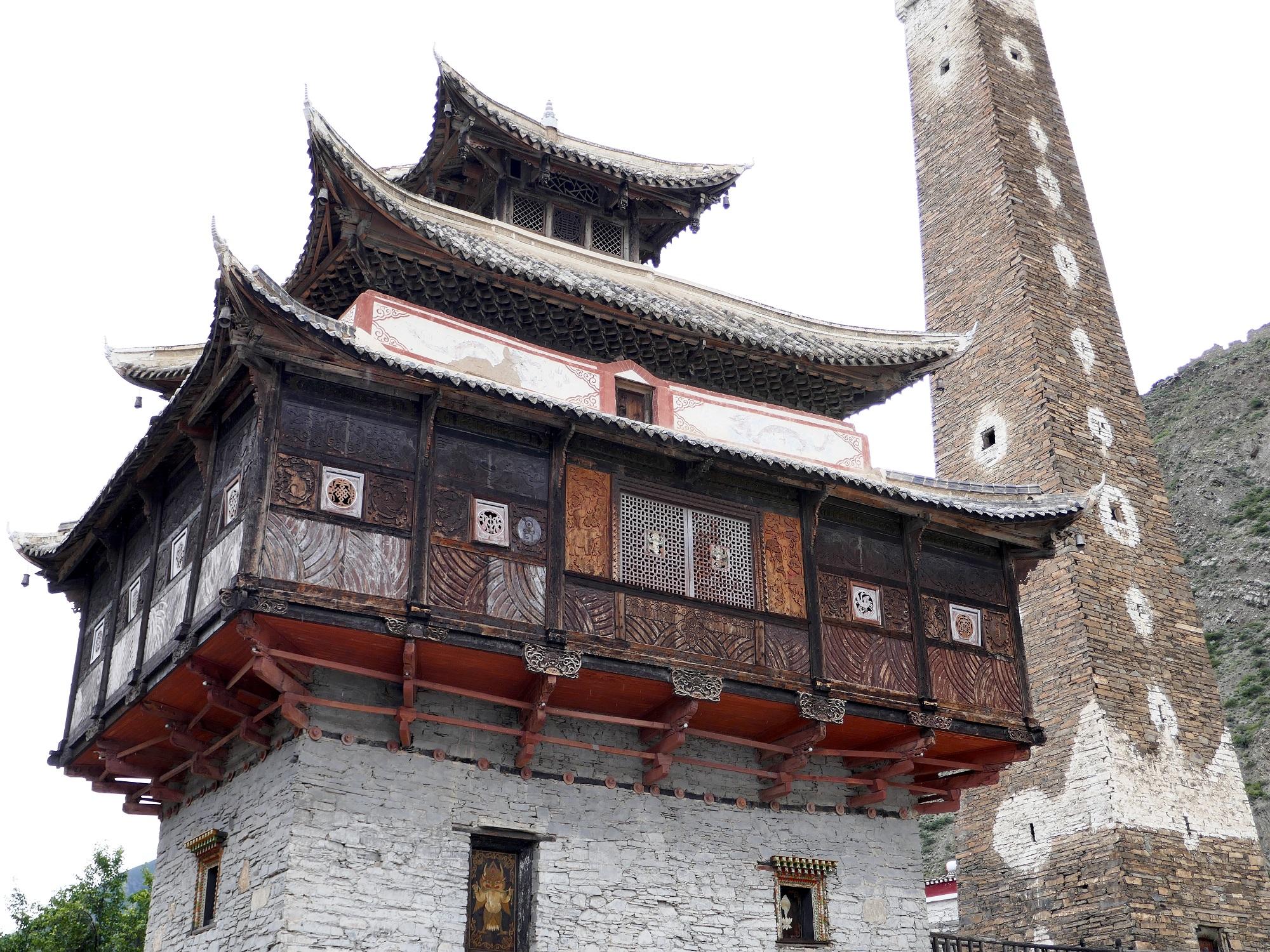 Maison d'architecture chinoise surplombée par une des impressionnantes tours de Damba – village de Tronang.